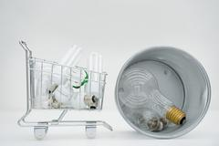 Shopping cart containing energy efficient light bulbs next to garbage can Stock Photos