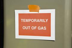 "Sign at gas station reading ""Temporarily out of gas"" - stock photo"
