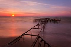 Beautiful sunrise landscape with a pier on background. long exposure. Stock Photos