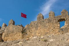 Ancient ruins of byzantine fortress with turkish flag in burch bay near simen Stock Photos
