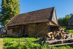 Old wooden farmhouse in the carpathians with the wood in the yard. Stock Photos