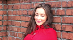 Beautiful girl in a red coat on a brick wall background Stock Footage
