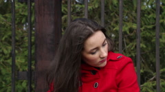 Beautiful girl in a red coat sitting on a brick parapet Stock Footage