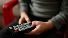 Child plays with a TV controller - boy sits - detail of the remote TV controller Stock Footage