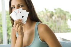 Teenage girl holding cards in front of face, all aces, looking at camera Stock Photos
