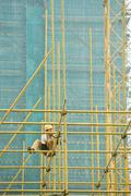 Man in hard hat perched on scaffolding, building in background Stock Photos