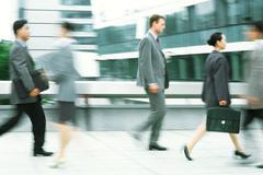 Male and female professionals walking on sidewalk, blurred motion - stock photo