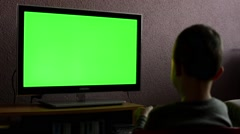Stock Video Footage of child (boy) watches television - child plays with a TV controller - green screen