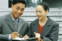 Male and female business associates looking at agenda together, smiling, man Stock Photos