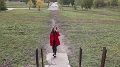 Beautiful girl in a red coat walks up the stairs Stock Footage