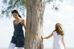 Two sisters walking around tree trunk, little girl touching tree with hand Stock Photos