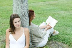 Mother and daughter leaning against tree trunk, woman reading book, teen girl Stock Photos