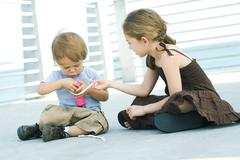 Little girl helping younger brother inflate balloon with air pump - stock photo