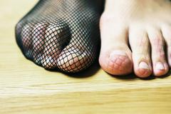 Woman wearing fishnet stocking on one foot, patterned imprint on bare foot, - stock photo