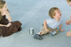 Little boy holding tin can phone, having tantrum, mother and sister watching Stock Photos