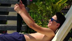 Young teenager taking selfie photo with smartphone during sunbath on sunbed HD - stock footage