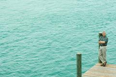 Man standing on corner of dock, looking away, high angle view Kuvituskuvat