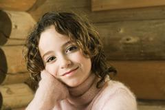 Girl leaning head on hand, smiling at camera - stock photo