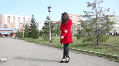 Beautiful girl in the red coat is waiting, standing in the alley in the park Stock Footage