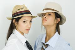 Two young female friends wearing hats and ties, both looking at camera - stock photo