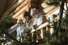 Three preteen or teen girls standing on deck of log cabin, looking away, low Stock Photos