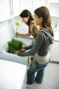 Mother and daughter standing together, placing wheat grass and gerbera daisy in - stock photo