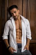 sexy handsome young man standing in white open shirt with a smile - stock photo