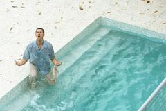 Man splashing in pool, fully clothed, shouting and gesticulating, high angle - stock photo