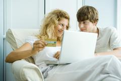Woman and teen son using laptop, making on-line purchase with credit card Stock Photos