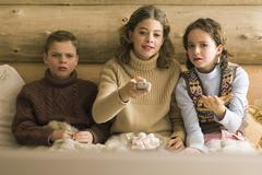 Three young siblings watching TV, teen girl changing channel while brother and Stock Photos