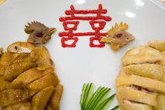 Close-up of cooked chickens on plate with Chinese ideogram - stock photo