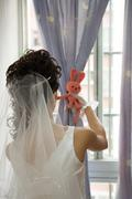 Bride facing window, tying curtain with stuffed toy, rear view Stock Photos