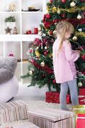 little girl at home decorating the christmas tree - stock photo