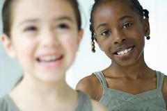 Two girls smiling, one looking at camera, selective focus - stock photo