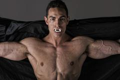 naked muscular fit young man in briefs posing as a vampire or dracula - stock photo