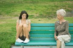Teenage girl sitting apart from grandmother on bench, both frowning - stock photo