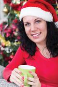 Women in christmas night drinking hot tea, in the background christmas tree Stock Photos