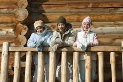 Three preteen or teen girls standing on deck of log cabin, looking away, low Stock Photos