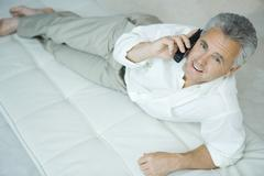 Mature man lying on chaise longue using cordless phone, looking up at camera Stock Photos