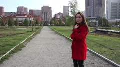 Beautiful girl in red coat goes on a path in a park Stock Footage