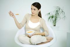Young woman sitting in chair, holding cereal bowl, looking at spoon Stock Photos
