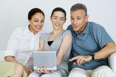 Teen girl watching portable DVD player with her parents, all smiling Stock Photos
