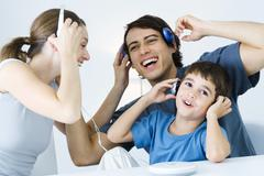 Family listening to CD player together, father and son using wireless headphones Stock Photos