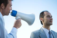 Businessman standing beside colleague, shouting into megaphone Stock Photos