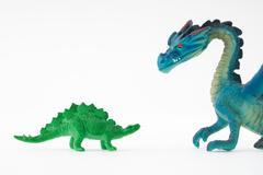 Toy dinosaur facing toy dragon - stock photo