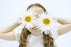 Little girl holding gerbera daisies in front of eyes, smiling, portrait Stock Photos