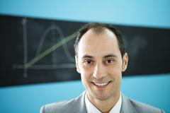 Man smiling at camera, diagram drawn on blackboard in the background - stock photo