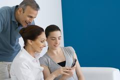 Family looking at cell phone together, smiling Stock Photos