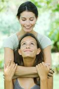 Mother embracing teen daughter from behind, both smiling at each other Stock Photos
