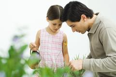Father and daughter looking down at flower, girl holding watering can - stock photo